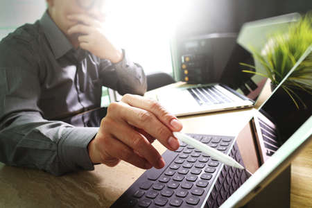 Outsource Developer working on marble Desk Working Laptop Computer Mobile Application Software and digital tablet dock smart keyboard,compact server,sun flare effect Standard-Bild