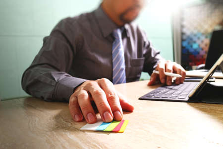 businessman working with new start up project.using smart phone digital tablet docking smart keyboard and laptop computer on marble desk,sun effect Stock Photo