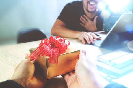 hombre rojo: Regalo Giving.business lado diseñador creativo dando su colega Regalo de Navidad en la oficina, película efecto de filtro Foto de archivo