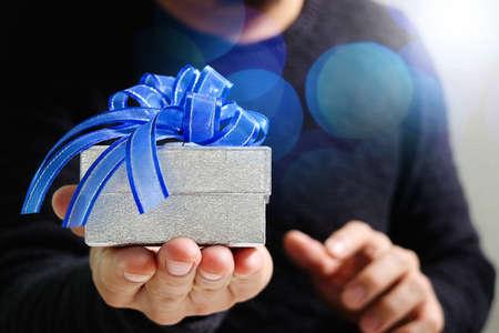 regalos, hombre de mano que sostiene una caja de regalo en un gesto de fondo giving.blured, el efecto bokeh