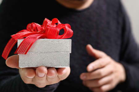 gift giving: gift giving,man hand holding a gift box in a gesture of giving.blurred background,bokeh effect