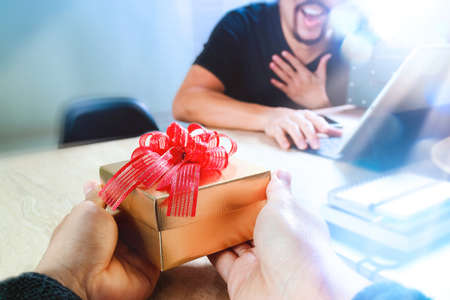 Gift Giving.business creative designer hand giving his colleague Christmas present in office,filter film effect Stock Photo - 65502317