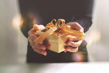 贈答、人間手ジェスチャーで giving.blurred 背景のボケ効果のゴールドのギフト ボックス