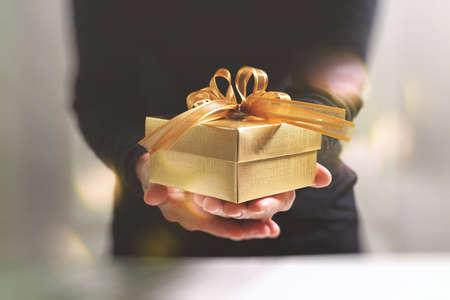 Dono che dà, mano dell'uomo in possesso di un contenitore di regalo d'oro in un gesto di dare. Sfondo sfocato, effetto bokeh Archivio Fotografico