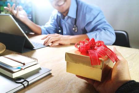 Gift Giving.Patient hand of Team geeft een cadeau aan een verraste arts in het ziekenhuis kantoor, filter film effect Stockfoto