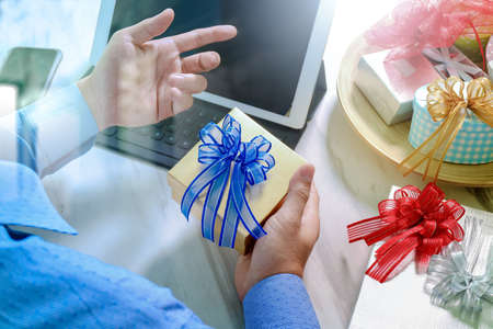 Gift Giving.Patient hand or Team giving a gift to a surprised Medical Doctor in hospital office