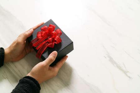 cadeau donnant, l'homme main tenant une boîte-cadeau dans un geste de donner sur blanc marbre gris fond de tableau