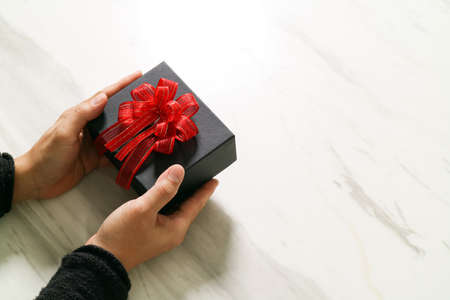 hand holding: gift giving,man hand holding a gift box in a gesture of giving on white gray marble table background