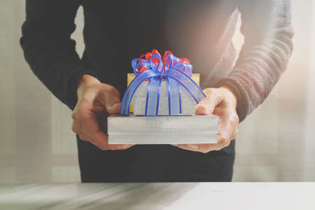 gift giving,man hand holding a gift box in a gesture of giving.blurred background,bokeh effect