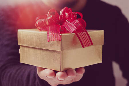 gift giving,man hand holding a gift box in a gesture of giving.blured background,vintage effect