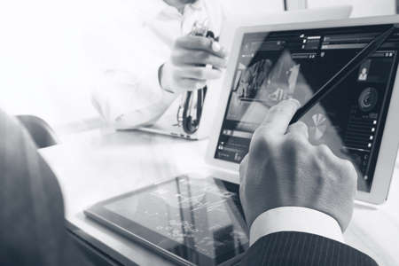 Medical technology network team meeting concept. Doctor hand working with smart phone modern digital tablet and laptop computer with graphics chart interface, double exposure effect photo, black white