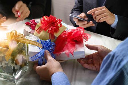 Regalo que da la mano creativa con teléfono inteligente y trabajador de elegir el regalo co. la entrega de regalos, fiestas en la oficina, en la reunión de la mesa de mármol, el efecto de película de filtro