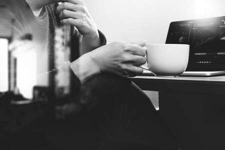 consultant: success businessman hand using smart phone,digital tablet docking smart keyboard,coffee cup on wooden desk,black white