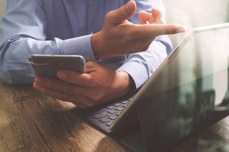 keyboard: success businessman hand using smart phone,digital tablet docking smart keyboard,on wooden desk,filter effect