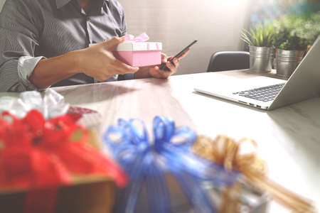 Gift giving Creative Hand choosing and hand with gift. Gift delivery, surprise,laptop computer and smart phone on mable desk,filter film effect 写真素材 - 121753523