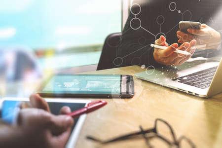 Foto website grafisch ontwerper de hand ontmoeting team met een nieuw project moderne studio.Modern laptop digitale tablet smartphone op marmeren table.Books papieren documenten, zon flare effect