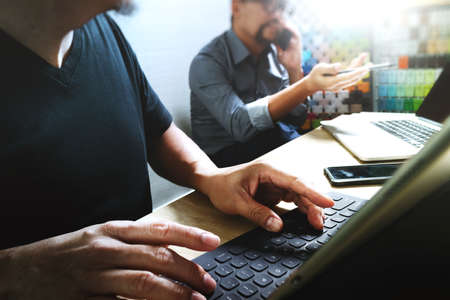 webmaster website: Coworking process, entrepreneur team working in creative office space. using digital tablet docking keybord and laptop with smartphone on marble desk,light beam effect