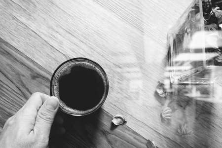 grunge backgrounds: Hand holding Coffee cup or tea ,glass vase dry flower herbs, on wooden table,filter effect,top view,black white Stock Photo