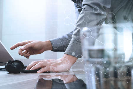 Man using VOIP headset with digital tablet computer docking smart keyboard, concept communication, it support, call center,digital screen graphic virtual icons,graph,diagram