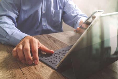 keyboard: success businessman using smart phone,digital tablet docking smart keyboard,on wooden desk,filter effect