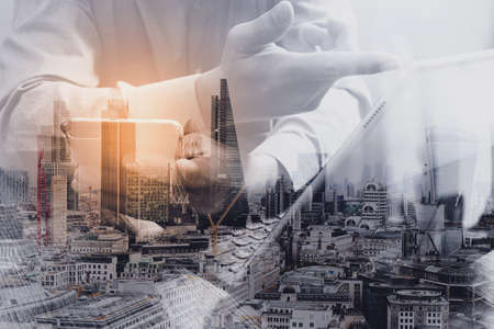 스마트 전화, 디지털 태블릿 도킹 스마트 키보드를 사용 하여 성공 사업가의 이중 노출 런던 건물, 도시, omnichannel 스마트 키보드