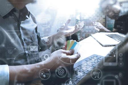 Co 労働者デザイナー手モバイル決済オンライン ショッピングを利用して、オムニ チャネルに、近代的なオフィスの木製デスク、アイコン グラフィ 写真素材