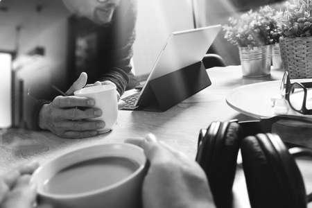 co werkende website ontwerpers werken op kantoor en het houden van een kopje koffie, werken aan slimme telefoon en digitale tablet-computer docking op slimme toetsenbord, zwart wit