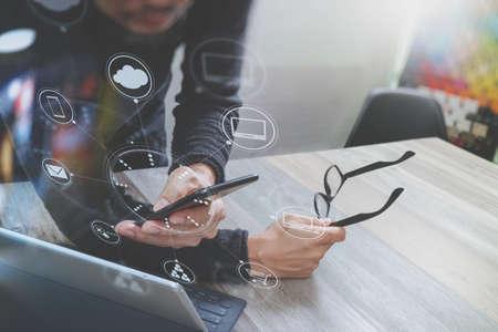 Zakenman hand gebruik mobiele betalingen online winkelen, omni kanaal, in moderne kantoor houten bureau, pictogrammen grafisch interface scherm, bril Stockfoto