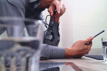 negocios internacionales: La mano de negocios usando los pagos móviles de compras en línea, lápiz, canal omnidireccional, el ordenador portátil en el escritorio de madera en la oficina moderna, efecto de filtro