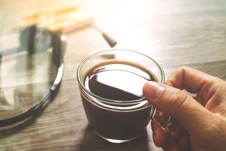 Hand holding Coffee cup or tea and voip headset,memo book on wooden table,filter effect