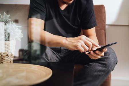 Progettista della mano dell'uomo con phon intelligente per i pagamenti mobili di shopping on-line, canale omni, seduto sul divano in salotto, in rattan vaso con piante e vassoio in legno sul tavolo, filtro Archivio Fotografico - 70550463