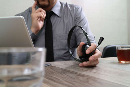 business man using VOIP headset with digital tablet computer docking smart keyboard, concept communication, it support,on wood desk Stock Photo