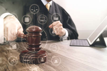 Hands of businessman using mobile phone in modern office with laptop and digital tablet computer with VR icon diagram Stock Photo