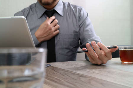 report icon: success businessman hand using smart phone,digital tablet docking smart keyboard,coffee cup on wooden desk