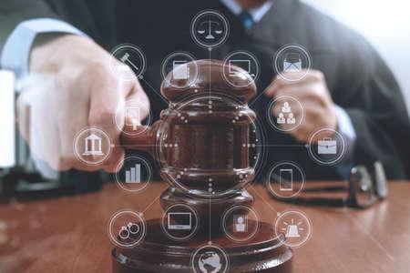 rechtvaardigheid en recht concept.Male rechter in een rechtszaal slaan van de hamer, het werken met digitale tablet computer docking toetsenbord op houten tafel, virtual-interface grafische pictogrammen diagram