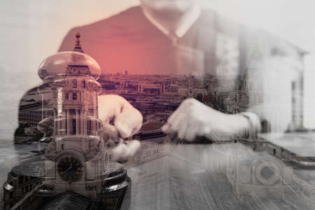 double exposure of justice and law concept.Male judge in a courtroom with the gavel,working with digital tablet computer docking keyboard on wood table,eyeglass,London architecture city Stock Photo
