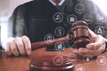 justice and law concept.Male judge in a courtroom striking the gavel,working with digital tablet computer docking keyboard on wood table,virtual interface graphic icons diagram