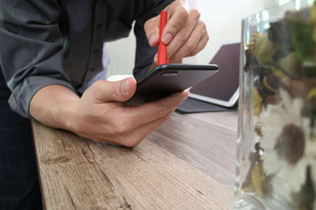 customer: businessman hand with pen using smart phone,mobile payments online shopping,omni channel,digital tablet docking keyboard computer,flower glass vase on wooden desk Stock Photo