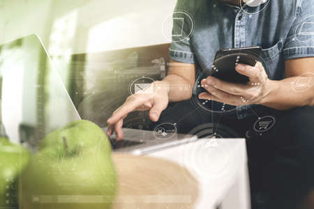 customer: designer man hand using laptop compter and mobile payments online shopping,omni channel,sitting on sofa in living room,green apples in wooden tray,graphic interfce icons virtual screen