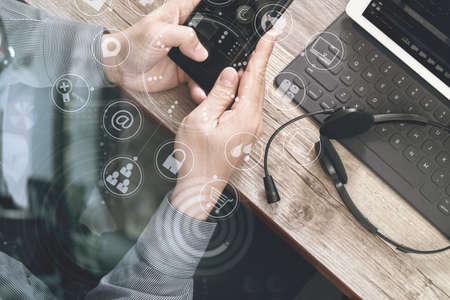 Vista dall'alto della mano dell'uomo con l'auricolare VOIP con la tastiera di docking del calcolatore digitale del ridurre in pani, telefono astuto, comunicazione di concetto, sostegno, call center e servizio di assistenza al cliente sul tavolo di legno, schermo delle icone dell'interfaccia virtuale Archivio Fotografico