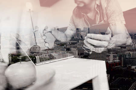 internet search: double exposure of hipster hand using laptop compter and mobile payments online business,eyeglasses,sitting on sofa in living room,green apples in wooden tray,London city buildings Stock Photo
