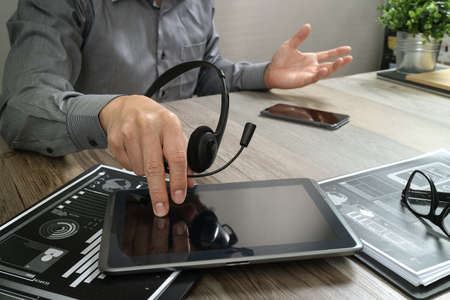 Zakenmanhand die VOIP-hoofdtelefoon met digitale tabletcomputer, document, conceptenmededeling, het steunen, call centre en de helpdesk van de klantendienst