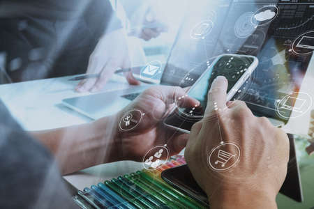 Designer Geschäftsmann Hand mit Smartphone, mobile Zahlungen Online-Shopping, omni-Kanal, digitale Tablet Docking-Tastatur Computer im modernen Büro auf Holz-Schreibtisch, virtuelle Schnittstelle Icons Bildschirm
