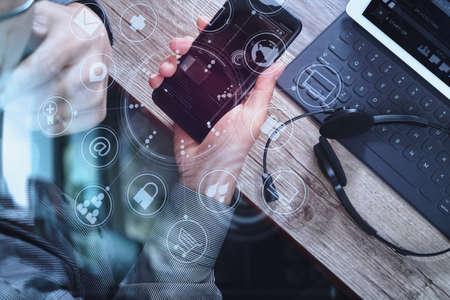 vista dall'alto della mano uomo utilizzando l'auricolare VOIP con tastiera docking digitale computer tablet, smart phone, concetto di comunicazione, supporto, call center e servizio clienti help desk sul tavolo in legno, schermo icone interfaccia virtuale
