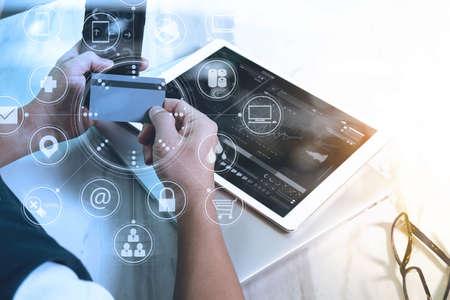 手自宅、オムニ チャネルのグラフィックス インターフェイス画面でクレジット カードを保持しているがヘッドフォンで音楽を聴く若者ショッピン 写真素材