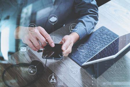 vista dall'alto della mano uomo utilizzando l'auricolare VOIP con tastiera docking digitale computer tablet, smart phone, concetto di comunicazione, supporto, call center e servizio clienti help desk sul tavolo in legno, schermo icone interfaccia virtuale Archivio Fotografico