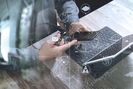 Draufsicht der Mannhand unter Verwendung des VOIP-Kopfhörers mit digitaler Tablet-Computerkopftastatur, intelligentem Telefon, Konzeptkommunikation, es stützt, Call-Center und Kundendienst-Service-Schreibtisch auf Holztisch, Ikonenschirm der virtuellen Schnittstelle Standard-Bild