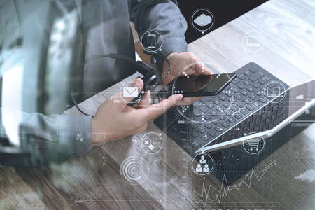 top view of man hand using VOIP headset with digital tablet computer docking keyboard,smart phone,concept communication, it support, call center and customer service help desk on wooden table,virtual interface icons screen