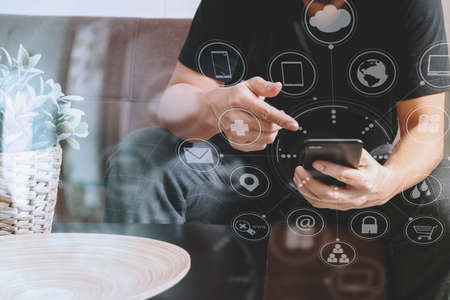 phon: designer man hand using smart phon for mobile payments online shopping,omni channel,sitting on sofa in living room,vase rattan with plant and wooden tray on table,virtual icons graphics interface screen