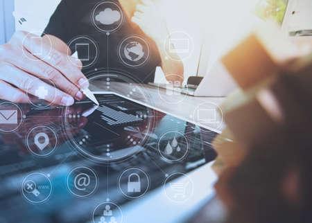 , Pantalla de iconos de interfaz virtual de negocios diseñador de la mano con teléfono inteligente, los pagos móviles de compras en línea, los canales de omni, tableta digital del ordenador del teclado de acoplamiento en la oficina moderna en escritorio de madera Foto de archivo